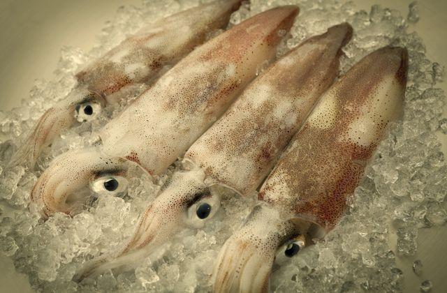 Замороженные или свежие кальмары сначала следует разморозить при комнатной температуре или в холодильнике, затем залить на одну минуту кипятком, слить кипяток и поместить их в холодную воду