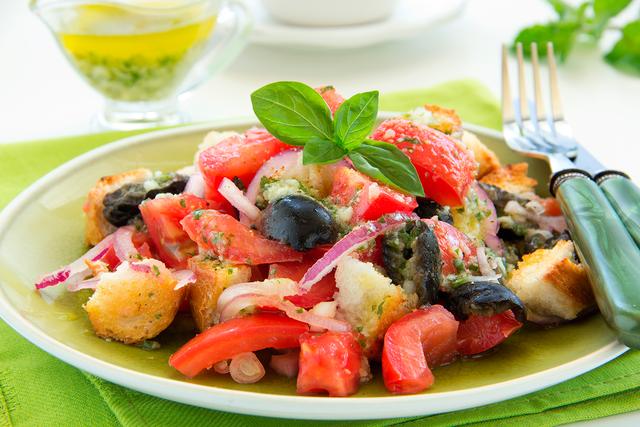 Посыпаем румяными сухариками овощи и украшаем базиликом — сытный салат в тосканском стиле готов