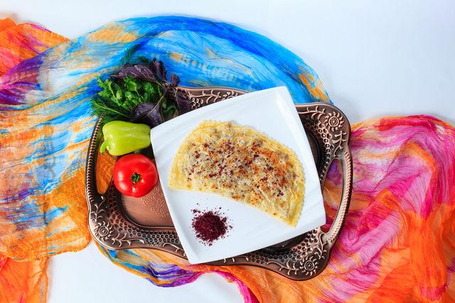 Сформировав традиционные полумесяцы и защипнув края, обжарьте кутабы на сухой сковороде и выложите на тарелки