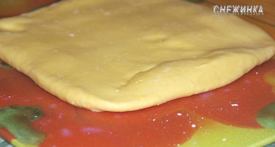 Через 30 минут достаем тесто из холодильника, кладем на раскатываемую поверхность таким же образом, как оно лежало на тарелке и раскатываем скалкой, не сильно, так, чтобы можно было вновь свернуть конвертом.