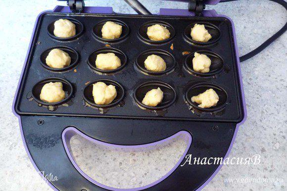 Разогреваем орешницу (у меня электрическая), немного смазываем маслом формочки. Пальцы смачиваем в воде и отщипываем от теста небольшие кусочки, формируем шарики и выкладываем в орешницу.