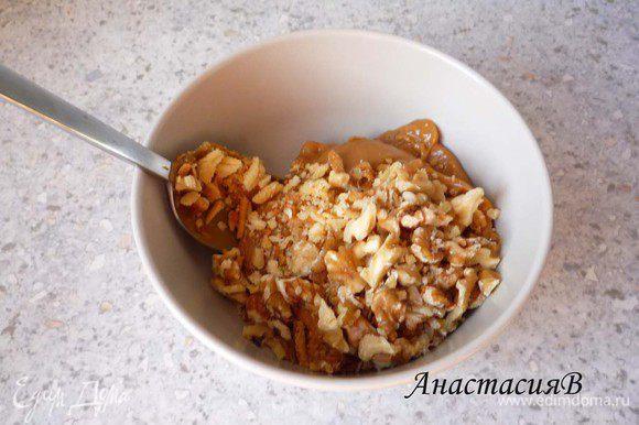 Добавляем к вареной сгущенке грецкие орешки и обрезки от теста, перемешиваем.