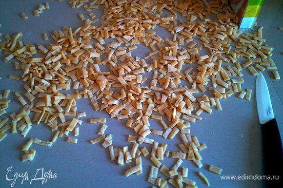 Настоявшееся тесто раскатываем в тонкий пласт (чем тоньше, тем лучше), нарезаем на полоски шириной 1,5 см и следом нарезаем на полоски шириной 0,5 см.