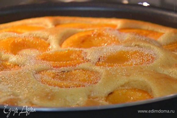 Через 25 минут приоткрыть духовку, посыпать пирог оставшимся сахаром и выпекать еще 10–15 минут.