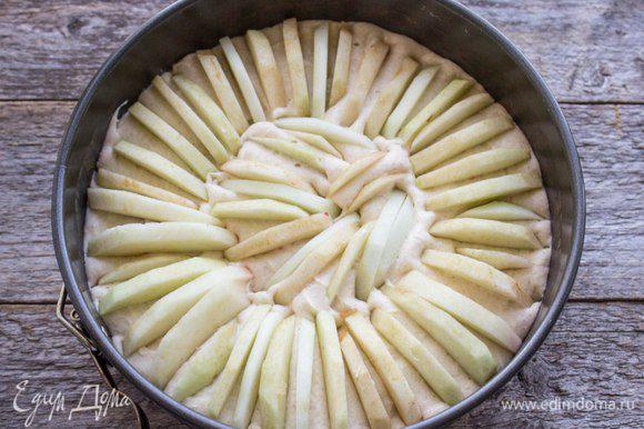 Белки взбить до крепких пиков, соединить с основной массой и аккуратно перемешать. Полученную массу выложить в форму для выпечки, выстеленную пергаментом. Яблоки очистить, освободить от семян и кожицы, нарезать тонкими дольками. Воткнуть в тесто по кругу выпуклой стороной вверх, плотно друг к другу по всей поверхности пирога.