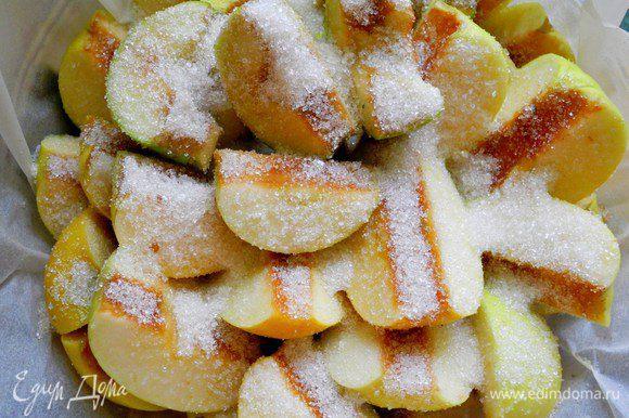 Сначала подготовим яблоки. Яблоки в исходном рецепте рекомендуются именно антоновские. Нарезаем их на четвертинки, удаляем сердцевину. Возьмем форму 26 см. Если есть чугунная сковородка с высокими бортиками, будет отлично. У меня форма из жаропрочного стекла. Застилаем форму бумагой для выпечки, сверху раскладываем кусочки сливочного масла и посыпаем половиной стакана сахара. Сверху плотно укладываем яблоки. Получается 2 слоя. Сверху снова посыпаем сахаром (полстакана).