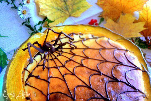 Decore o cheesecake com uma teia de aranha de chocolate derretido usando uma cornette de papel.  A aranha também é feita de chocolate derretido.