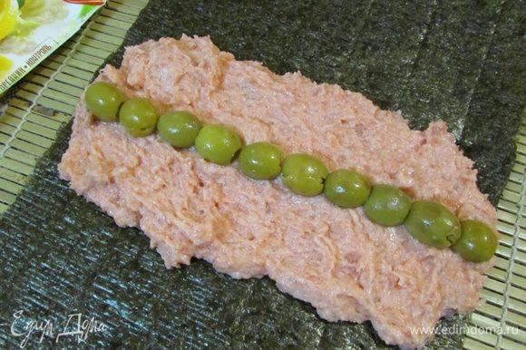 Сложить два листа нори внахлест. На листы выложить массу из форели, разровнять в форме прямоугольника. На рыбу выложить полоской маслины.