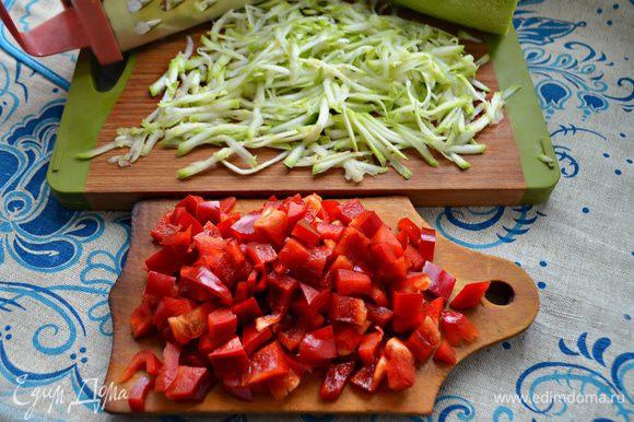 Для начинки помойте и натрите на крупной терке молодой кабачок. Два небольших перца также помойте и нарежьте небольшими кубиками.