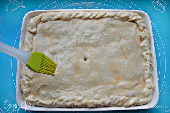 Накройте вторым пластом теста и защипните края. С помощью трубочки для коктейля сделайте отверстие в центре пирога. Дайте тесту немного подняться (15 мин.), смажьте желтком и посыпьте кунжутом.