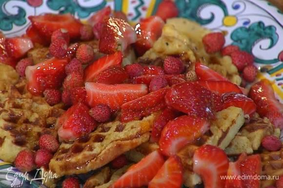 На готовые вафли выложить клубнику, полить кленовым сиропом и посыпать земляникой.
