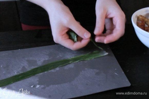 На край пера положить листочек мяты, сверху листочек кинзы.