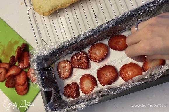 Клубнику нарезать на кружочки одинаковой толщины. Начинаем собирать торт. Форму, которую вы выберете, застелить внутри пищевой пленкой. На дно положить первый корж, распределить сверху крем, следом клубнику. Так проделать с каждым слоем. Сверху накрыть пищевой пленкой и убрать в холодильник минимум на 2 часа.